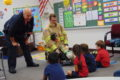 ANNE EICKSTADT PHOTO Belvidere Republican Firefighter Jeff describes what each part of the firefighting gear is for as Firefighter Glenn stays low to avoid intimidating the preschoolers in the class at St. James.