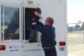 ANNE EICKSTADT PHOTO Belvidere Republican 	Firefighter Chad Cunningham assists a Seth Whitman Elementary School second grader to 'escape' through the window of the BFD Fire Safety House.