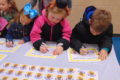 ANNE EICKSTADT PHOTO Belvidere Republican Students at Seth Whitman Elementary School sign a school bus safety pledge during the Safety Dog Bus Tour visit.