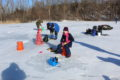 ANNE EICKSTADT PHOTO Belvidere Republican 	Gianna Roby, age 10, and Helena Roby, age 7 ½, are enjoying their ice fishing experience while Tod Todd (in blue) uses the Vex Box to spot fish.