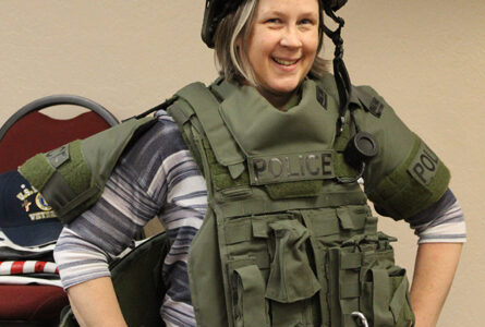 Citizens Police Academy student Chris Gardner tries on the SWAT protective vest and helmet.